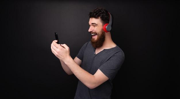 Foto de um homem feliz com barba, música alegre e usando o telefone sobre um fundo isolado