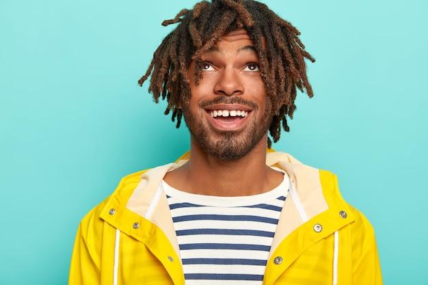 Foto de um homem feliz com dreads, tem uma expressão positiva, focado acima, usa um macacão de marinheiro e uma capa de chuva amarela, isolado sobre um fundo azul