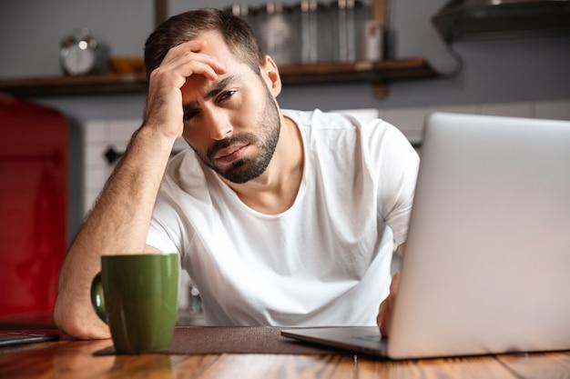 Foto de um homem frustrado de 30 anos vestindo uma camiseta casual usando um laptop prateado enquanto está sentado à mesa em um apartamento moderno