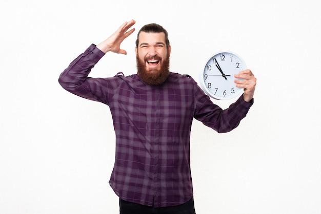 Foto de um homem frustrado segurando um relógio de parede e gesticulando