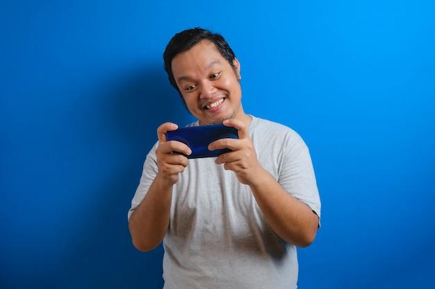 Foto de um homem gordo asiático vestindo uma camiseta cinza, parecendo feliz jogando um jogo em seu smartphone. os homens mostram gestos confiantes. isolado em um fundo azul