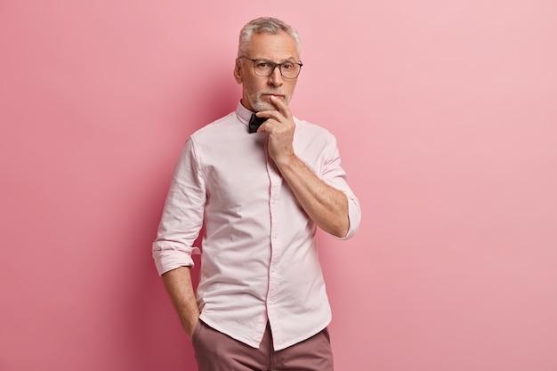 Foto de um homem idoso atencioso com a mão na boca, a outra no bolso da calça, com expressão pensativa