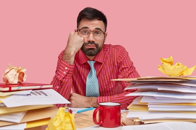 Foto de um homem insatisfeito e sonolento segura a mão na bochecha, parece com uma expressão triste, usa camisa rosa, óculos grandes, bebe café ou chá, tem muitos papéis na mesa
