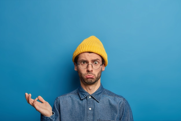 Foto de um homem intrigado e chateado levantando a palma da mão, parece com uma expressão triste e incomodada, usa chapéu amarelo, camisa jeans