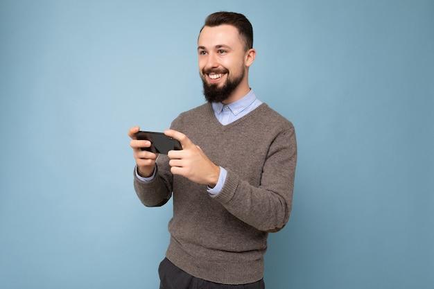 Foto de um homem jovem e feliz com barba por fazer, uma jovem morena bonita, vestindo um suéter cinza e azul todos os dias