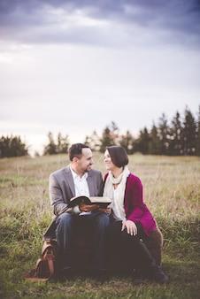 Foto de um homem lendo um livro para uma mulher sob um céu nublado