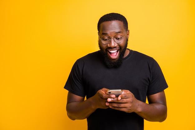 Foto de um homem mestiço bonito e engraçado moreno com uma camiseta, muito feliz por receber uma notificação positiva de feedback isolado na parede amarela vívida
