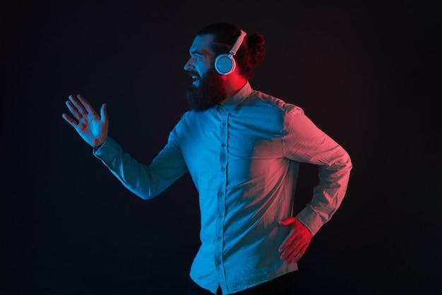 Foto de um homem moderno com barba usando fones de ouvido sem fio e correndo sobre um fundo escuro com luz de néon