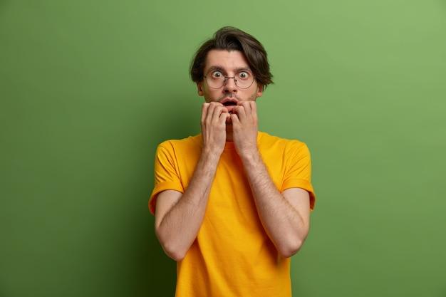 Foto de um homem nervoso preocupado que morde as unhas e o encara com expressão de medo, assustado com algo assustador, usa óculos redondos e camiseta amarela, posa contra a parede verde