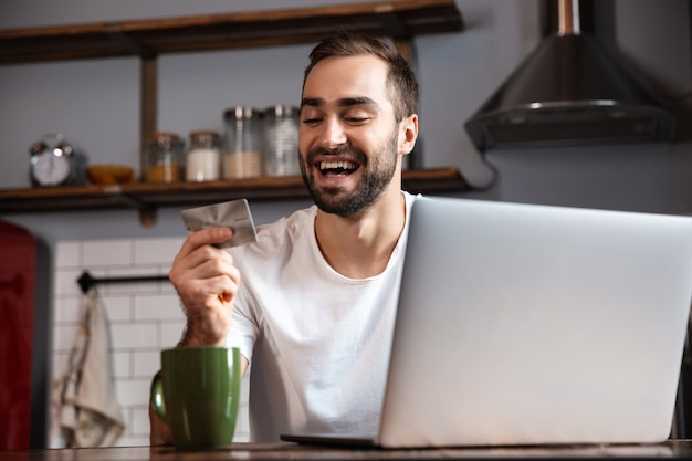 Foto de um homem otimista de 30 anos vestindo uma camiseta casual usando um laptop prateado enquanto está sentado à mesa em um apartamento moderno