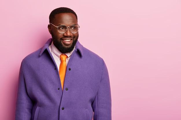 Foto de um homem positivamente de pele escura em pé, pensativo, sorrindo com os dentes, olha para o lado, usa roupas formais e gravata