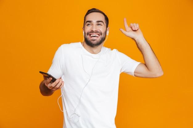 Foto de um homem positivo dos anos 30 ouvindo música usando fones de ouvido e telefone celular, isolada