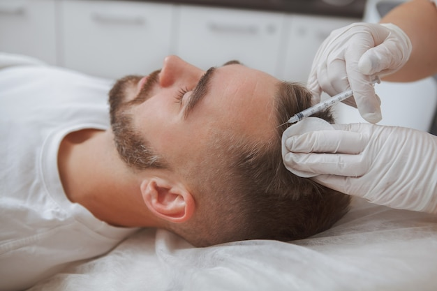 Foto de um homem recebendo tratamento com injeções de queda de cabelo por esteticista