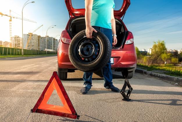 Foto de um homem segurando a roda sobressalente contra um carro quebrado