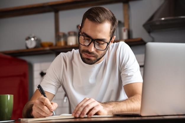 Foto de um homem sério de 30 anos usando óculos escrevendo anotações enquanto usa um laptop prateado na mesa da cozinha