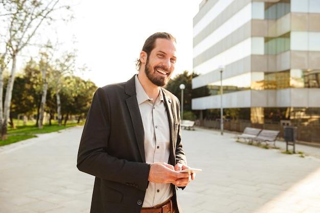 Foto de um homem sorridente caucasiano de 30 anos em um terno de negócios olhando para você e segurando um smartphone, enquanto caminhava perto de um prédio de escritórios