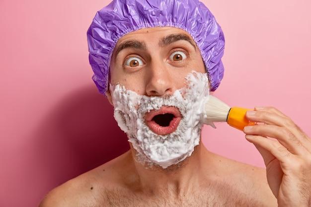 Foto de um homem surpreso usando touca de banho, fica de pé com o torso nu, se arruma para o dia, faz a barba por fazer, aplica creme de barbear com pincel, tem olhar maravilhado