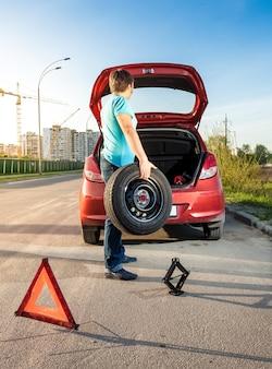 Foto de um homem tirando a roda sobressalente do porta-malas