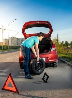 Foto de um homem trocando uma roda perfurada em um carro quebrado