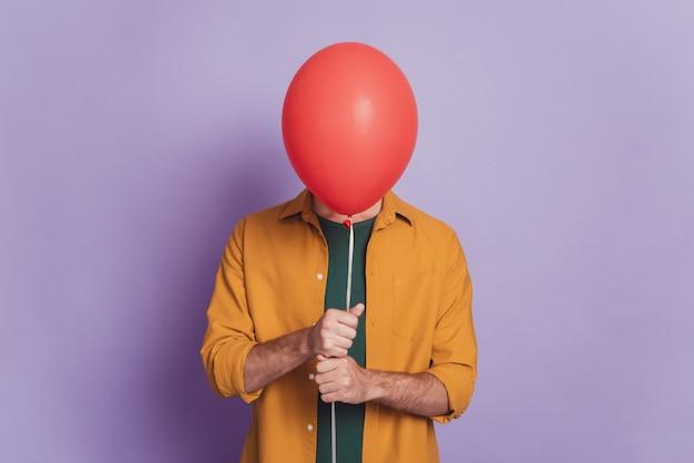 Foto de um hóspede tímido segurando um balão vermelho, escondendo o rosto, vestindo uma camisa posando em fundo violeta