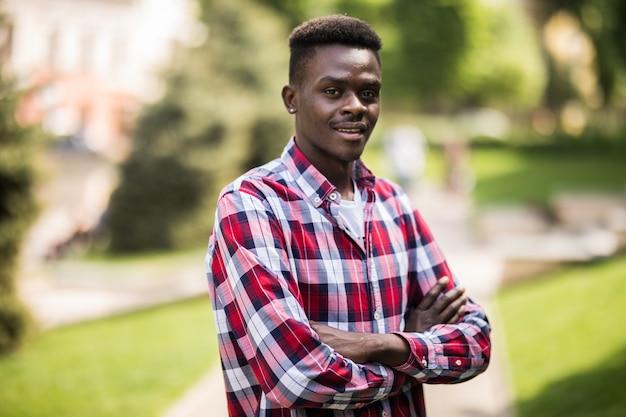 Foto de um jovem africano andando na rua em pé com os braços cruzados.