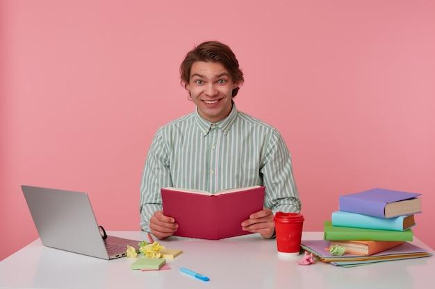 Foto de um jovem alegre de óculos, sentado em uma mesa com livros, trabalhando em um laptop, segurando o livro aberto, olha para a câmera e sorrindo, isolado sobre fundo rosa.