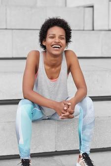 Foto de um jovem alegre de pele escura com cabelo preto crespo, com um sorriso largo, vestido com colete e leggings casuais, senta-se na escada, desfruta de um estilo de vida saudável, seu jogo de esporte favorito vitalidade, bem-estar