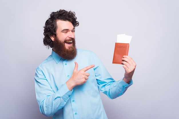 Foto de um jovem alegre segurando um passaporte com alguns ingressos e apontando para eles perto de uma parede cinza
