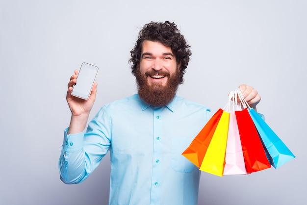 Foto de um jovem alegre segurando um telefone e, na outra, algumas sacolas de compras perto da parede cinza