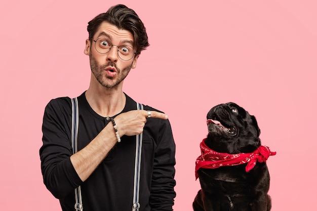 Foto de um jovem amante de animais de estimação surpreso que aponta para seu cão de raça, vestido com uma camisa preta, que se pergunta algo, indica o dedo indicador para prestar atenção ao animal, isolado sobre a parede rosa.