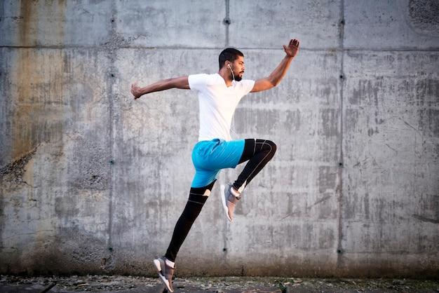 Foto de um jovem atleta esportivo pulando contra o fundo da parede de concreto