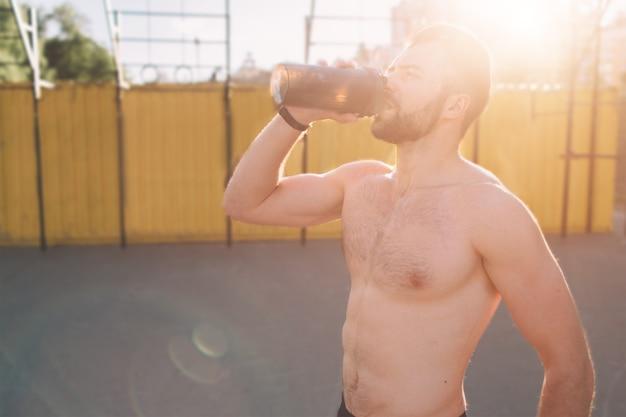 Foto de um jovem atlético após o treino. musculoso jovem e bonito bebe uma proteína. atleta atraente atlético sem camisa bebendo batido de nutrição esportiva no liquidificador