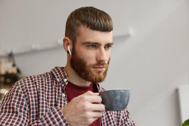 Foto de um jovem atraente ruivo barbudo segurando uma xícara de café cinza, reflete sobre os planos para amanhã e desviar o olhar, vestindo roupas básicas.