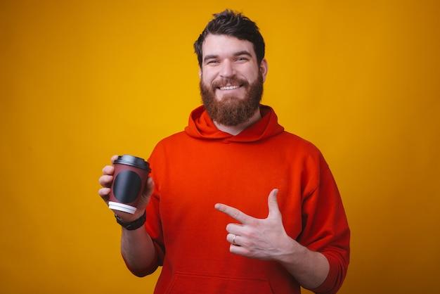 Foto de um jovem barbudo alegre está apontando para ele tirar a xícara de café.
