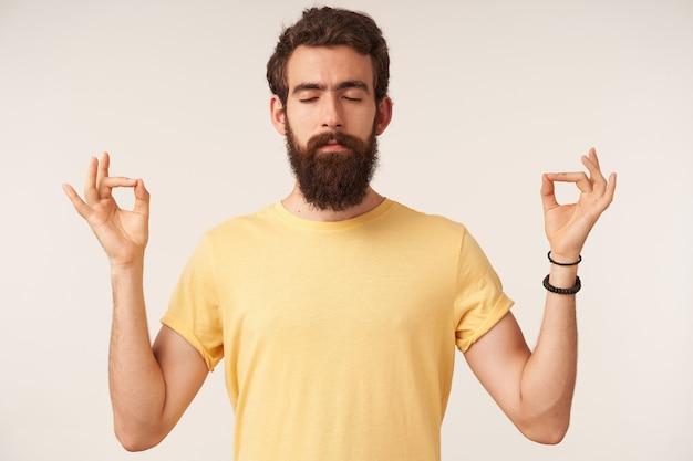 Foto de um jovem barbudo bonito meditativo com olhos fechados, emoção calma e pensamento profundo em pé