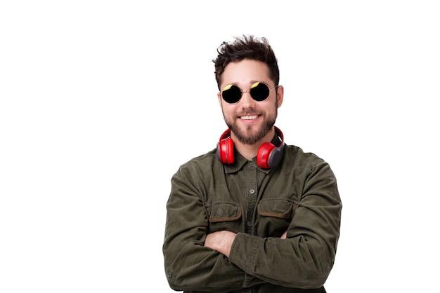 Foto de um jovem barbudo com óculos escuros e fones de ouvido, em pé com as mãos cruzadas na parede branca