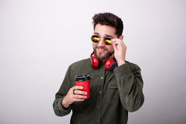 Foto de um jovem barbudo com óculos escuros e fones de ouvido, segurando uma xícara enquanto toca a moldura dos óculos de sol
