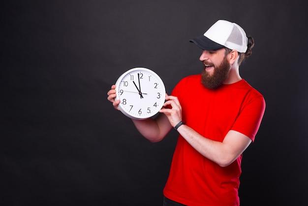 Foto de um jovem barbudo com uma camiseta vermelha e boné branco segurando um relógio às onze horas