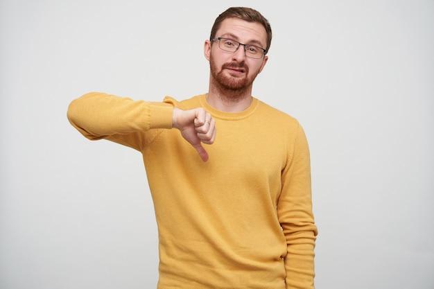 Foto de um jovem barbudo descontente com cabelo castanho curto torcendo a boca com beicinho e apontando com o polegar para baixo, vestindo um suéter mostarda em pé