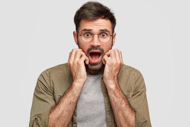 Foto de um jovem barbudo emocionado e assustado mantém o queixo caído, expressa medo e descrença, mantém as mãos perto da boca aberta, encara com olhar ansioso, isolado sobre uma parede branca
