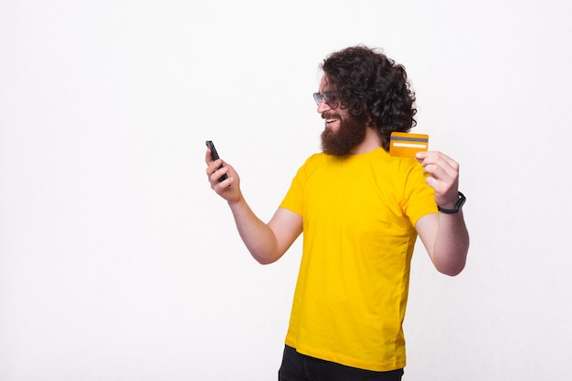 Foto de um jovem barbudo hippie com cabelo comprido e encaracolado usando smartphone e pagando online com cartão de débito