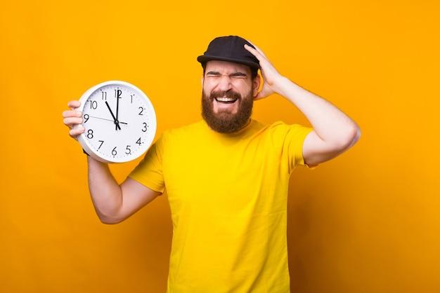 Foto de um jovem barbudo segurando um relógio de parede e fazendo um gesto frustrante. estou atrasado