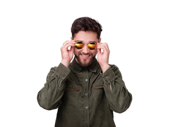 Foto de um jovem barbudo tocando a moldura dos óculos de sol, sobre fundo branco