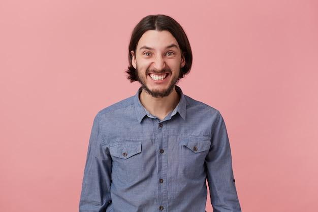 Foto de um jovem barbudo zangado com cabelo escuro comprido penteado de mau humor, parece zangado e descontente isolado sobre um fundo rosa.