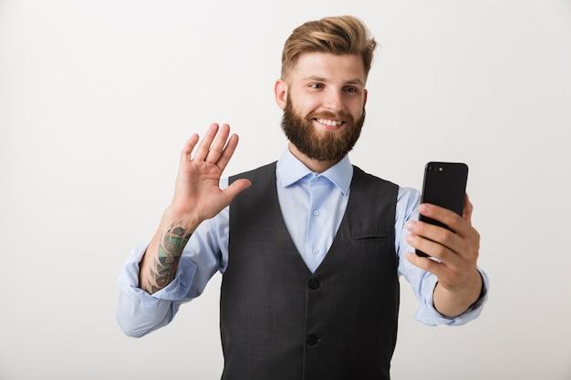 Foto de um jovem bonito barbudo em pé isolado sobre uma parede branca, usando telefone celular, falando acenando.