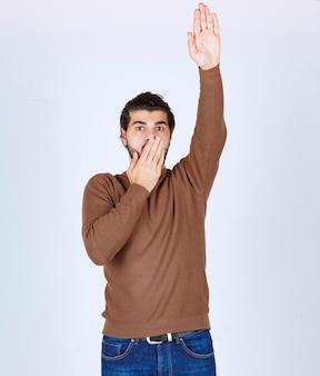 Foto de um jovem bonito de pé e levantando a mão. foto de alta qualidade