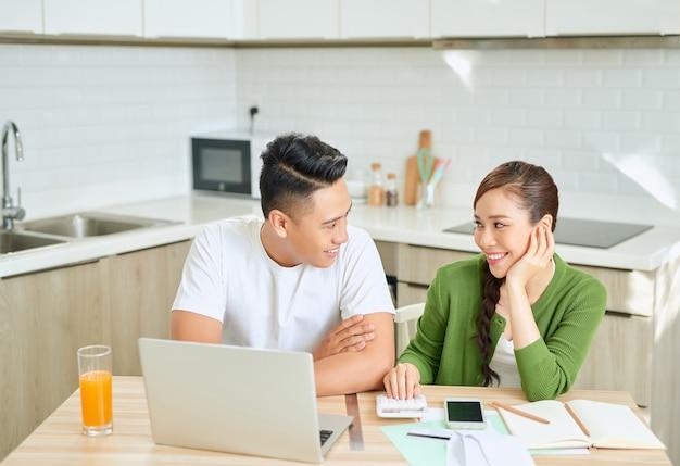 Foto de um jovem casal amoroso alegre usando laptop e analisando suas finanças com documentos. olhe para os papéis.