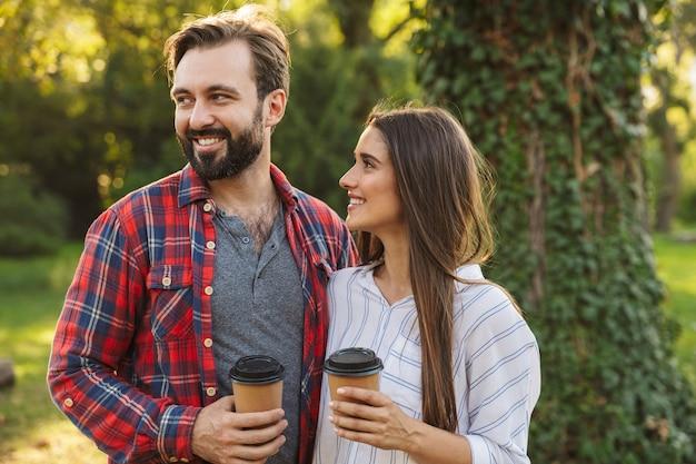 Foto de um jovem casal apaixonado, alegre, caminhando ao ar livre em uma floresta verde do parque natural, bebendo café.