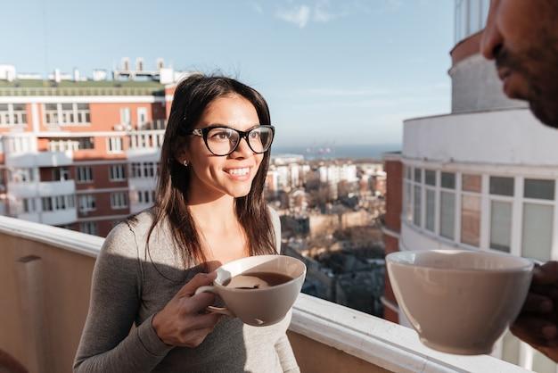 Foto de um jovem casal apaixonado, bebendo café em pé no telhado. olhem um para o outro.