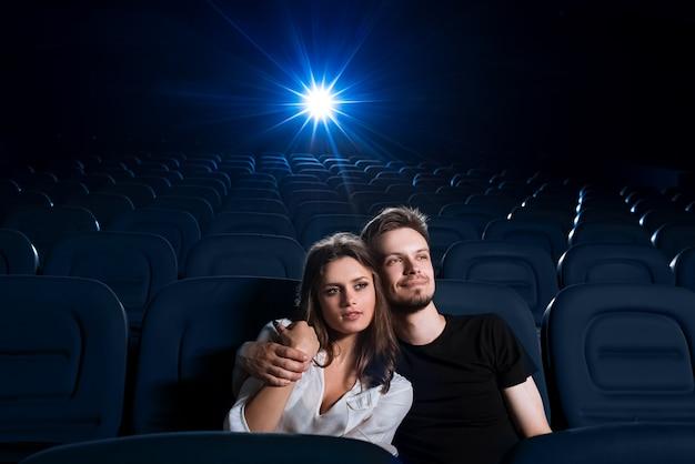 Foto de um jovem casal apaixonado ter um encontro no cinema assistindo a um filme